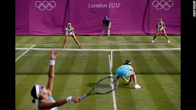 Yaroslava Shvedova of Kazakhstan serves next to her partner Galina Voskoboeva of Kazakhstan during the women's doubles tennis match against Maria Kirilenko and Nadia Petrova of Russia.