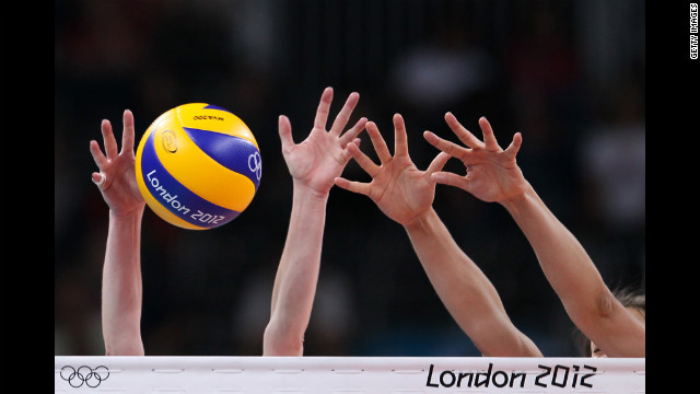 A detailed view of hands and the ball in the women's volleyball preliminary match between Great Britain and Algeria.