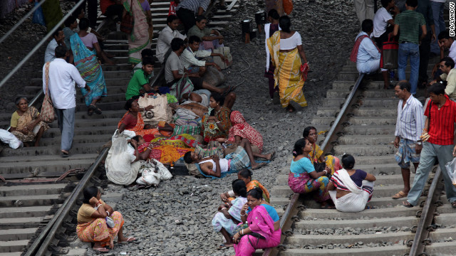 Passengers wait on the tracks for a train during a massive electricity failure at a station in Kolkata, formerly known as Calcutta, on Tuesday. India suffered its second huge, crippling power failure in two days Tuesday, depriving up to 600 million people of electricity and disrupting transport networks.