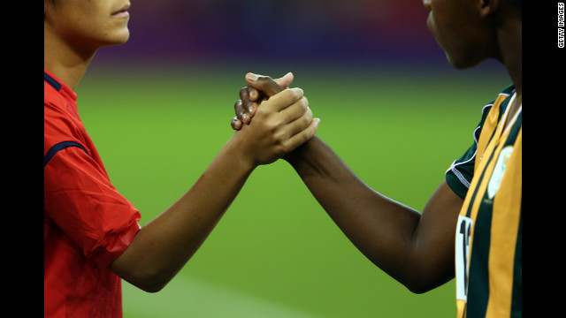 Japan and South African players shake hands before their women's football first-round match Tuesday.