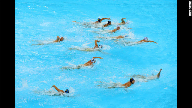 Australian and Kazakh athletes swim for the ball during a men's water polo preliminary round at Water Polo Arena in London.