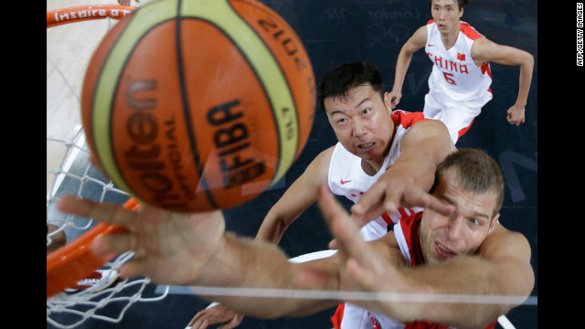 China's Wang Zhizhi, left, tries to block Sergey Monya of Russia from scoring during the men's preliminary round basketball match on Tuesday.