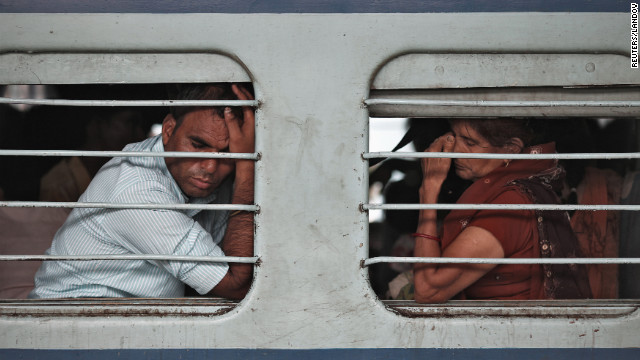 Passengers sit on a train with no electricity as power failures halt transportation across the country Tuesday.