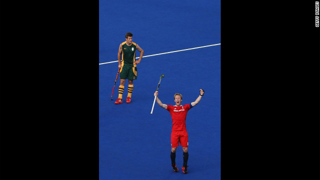 Captain Barry Middleton, in red, celebrates an equalizing goal in front of Lloyd Norris Jones of South Africa during their men's preliminary hockey match.