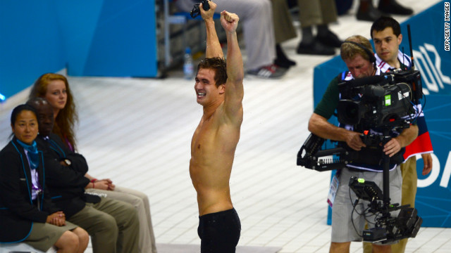 American swimmer Nathan Adrian raises his hands in triumph.