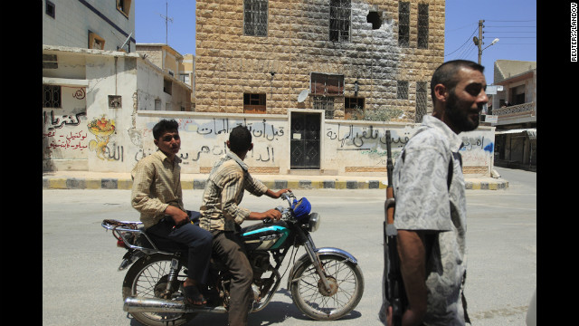 People and a member of the Free Syrian Army commute on Wednesday, August 1, past a building on the outskirts of Idlib that was hit by rocket fire Tuesday night by forces loyal to President Bashar al-Assad. Unrest spread across other volatile regions of the country as al-Assad's forces shelled targets and launched raids in and around Damascus, Homs, Daraa and Deir Ezzor.