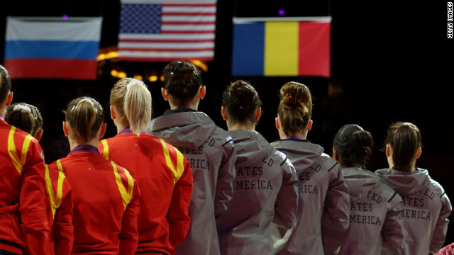The U.S. team, left, takes the podium after winning the gold medal in the women's gymnastics event. Russia took silver and Romania won the bronze.