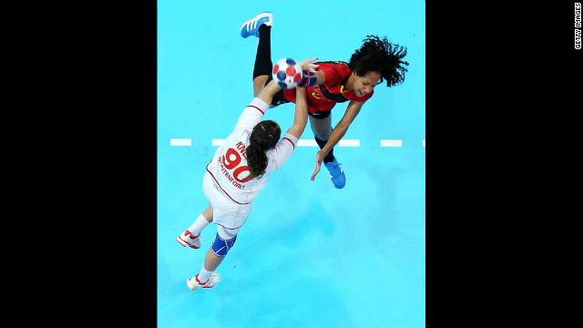 Carolina Morais of Angola throws over Milena Knezevic of Montenegro in a women's preliminary handball match Wednesday.