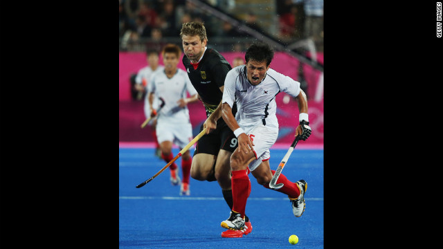 Germany's Moritz Fuerste, left, challenges South Korea's Jong Bok Cha, right, for the ball during the men's preliminary hockey match.