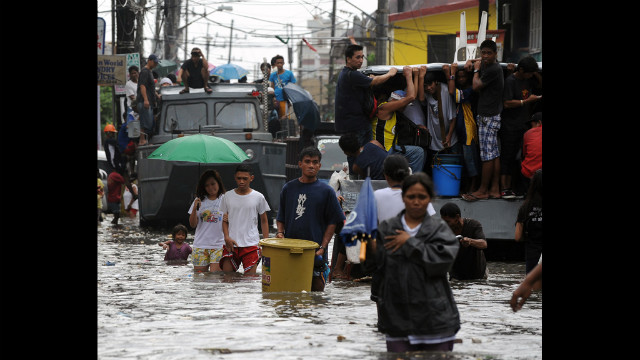 Residents maneuver through a flooded street Wednesday in Navotas. 