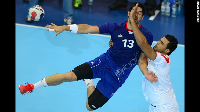 French centerback Nikola Karabatic, left, vies with a Tunisian opponent during a men's preliminary handball match.