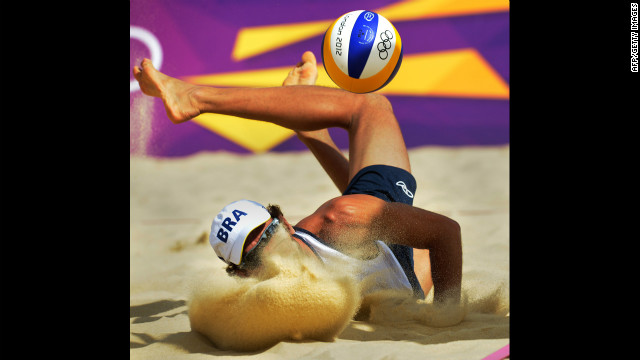 Brazil's Emanuel Rego lands after saving a ball during the men's beach volleyball preliminary phase match against Italy.