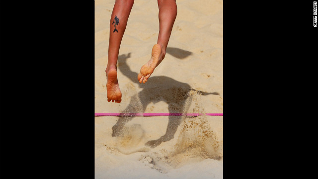 Italy's Greta Cicolari serves during a beach volleyball preliminary match against Canada.
