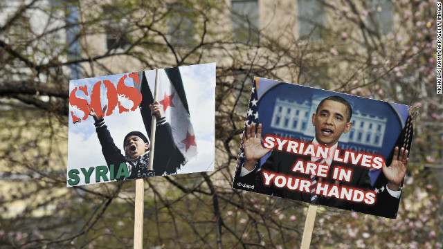 People hold signs during a rally in support of the Syrian opposition at Lafayette Park in front of the White House in March.