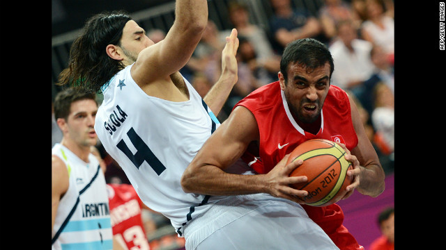 Tunisian forward Makram Ben Romdhane, right, vies with Argentine forward Luis Scola during the men's preliminary round group A basketball match.