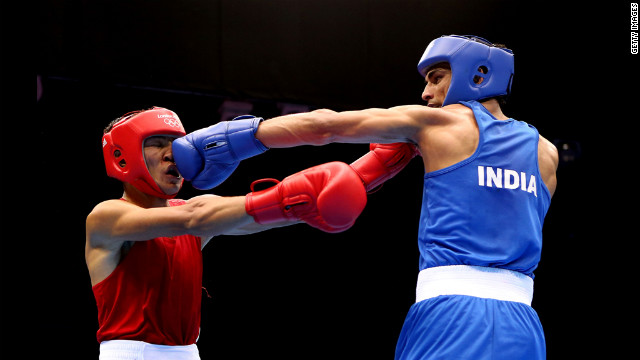 Kazakhstan's Gani Zhailauov, left, takes a hit from India's Bhagwan Jai during the men's lght bxing.