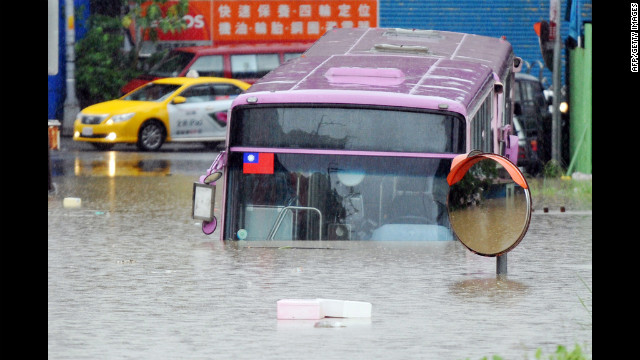 A bus sits half submerged on a flooded road in New Taipei City.