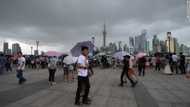 People walk along the Shanghai Bund on Thursday as storm clouds gather over the Huangpu River. The typhoon was expected to strike south of Shanghai later Thursday.