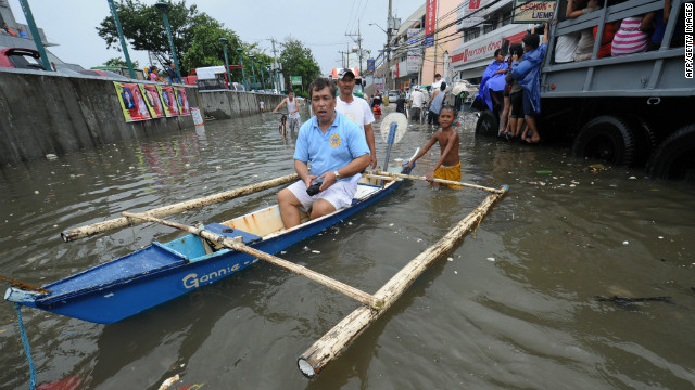 A resident rides in a banca on a flooded street in Navotas. 