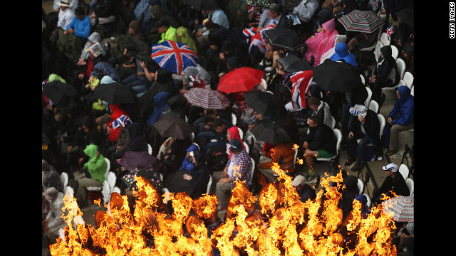 Fans take shelter from the rain, while the Olympic Cauldron remains aflame at Olympic Stadium.
