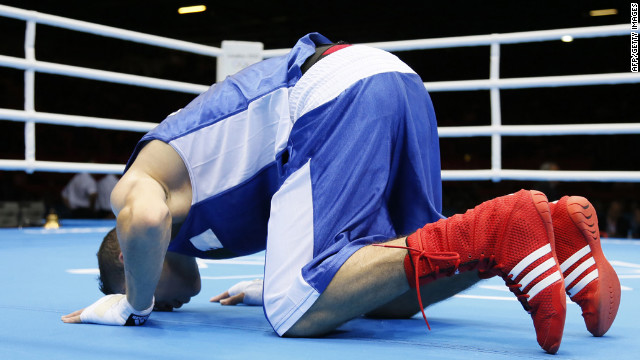 Algeria's Samir Brahimi kneels in prayer following his loss in the men's flyweight boxing match to Misha Aloian of Russia.