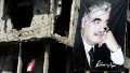 A poster of former Lebanese prime minister, Rafik Hariri, hangs beside a building riddled with bullet holes in Beirut.