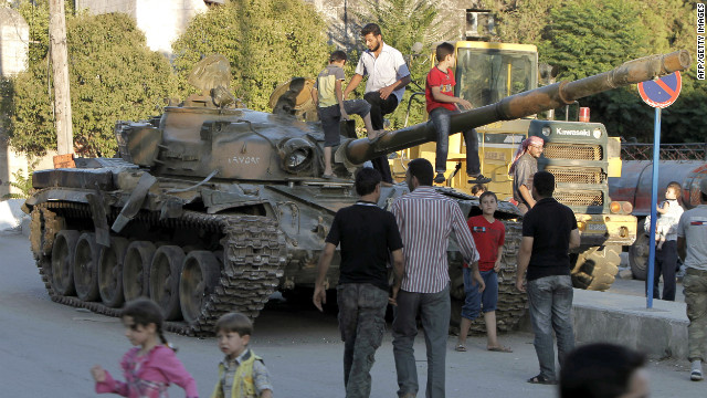 Syrians climb on an abandoned Syrian army tank north of Aleppo on Thursday, August 2.