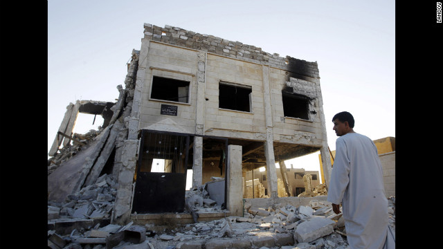 A man looks at a destroyed Syrian army compound in Azaz, 29 miles north of Aleppo on Friday, August 3.
