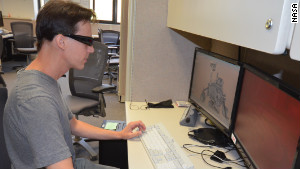Scott Maxwell wears 3-D glasses to simulate driving a Mars rover at JPL's Mission Operations area.