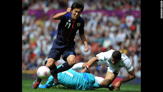 Japan's Kensuke Nagai, left, scores past Egypt's goalkeeper Ahmed Al-Shenawi, center, and Egypt's defender Saadeddine Saad, right, during the quarter final football match Saturday.