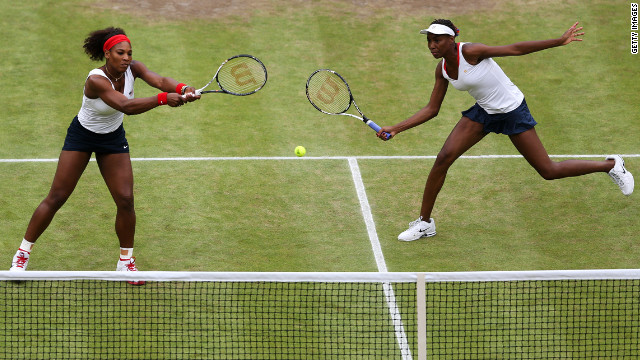 Serena Williams, left, and Venus Williams, right, return a shot during the women's doubles final.