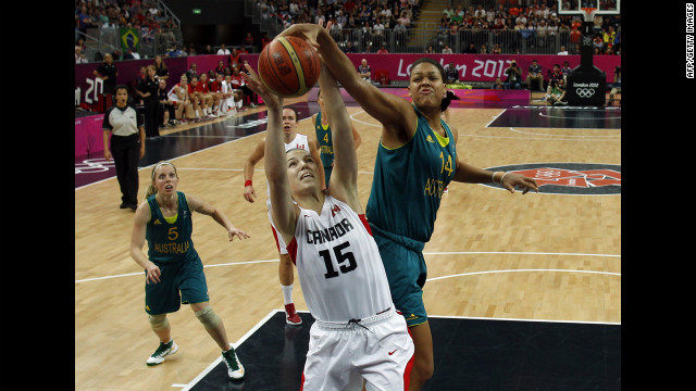 Canadian forward Michelle Plouffe, center, struggles with Australian center Elizabeth Cambage for control of the ball during the women's preliminary round group B basketball match.