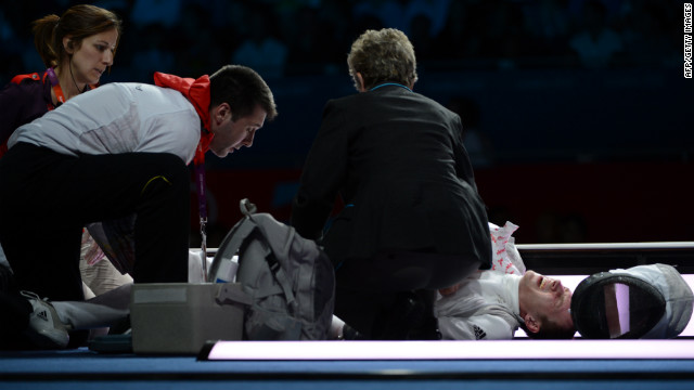 Germany's Sebastian Bachmann is treated by medical personnel after being injured during his bout with U.S. fencer Gerek Meinhardt during the men's foil team medal bronze match.