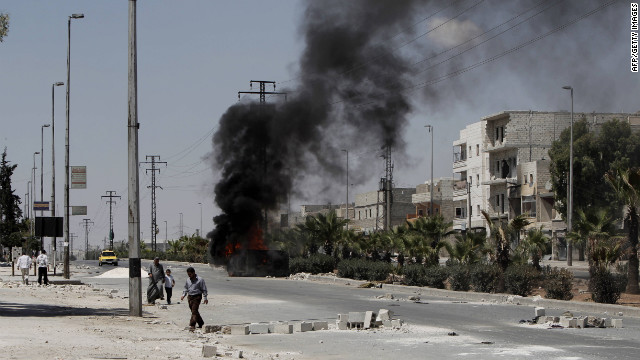 A vehicle burns as Syrians walk through debris from clashes between Syrian armed forces and rebels in th<br />