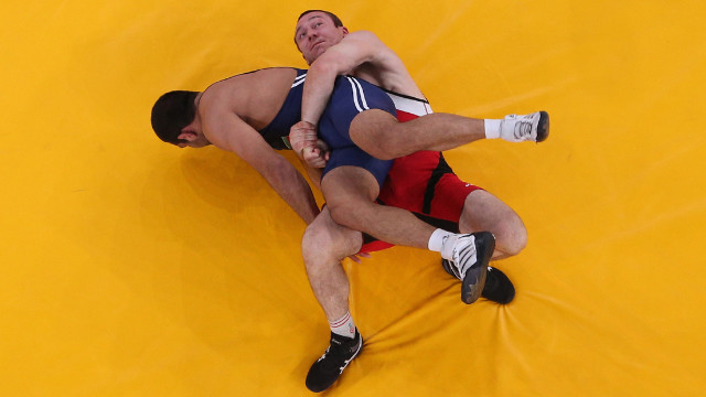 Aliaksandr Kikiniou of Belarus, in red, grapples with Emin Ahmadov of Azerbaijan in their men's Greco-Roman 74-kilogram wrestling bronze medal match.