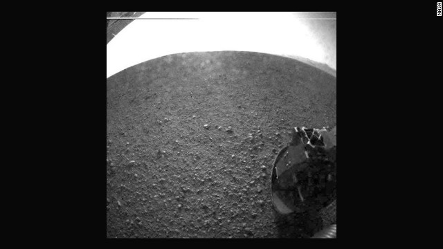 One of the first images taken by NASA's Curiosity rover, which landed on Mars early Monday, August 6. The clear dust cover that protected the camera during landing has been sprung open. Part of the spring that released the dust cover can be seen at the bottom right, near the rover's wheel.