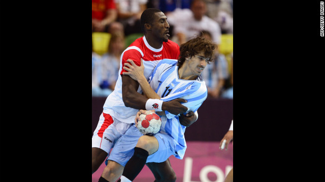Tunisia's Selim Hedoui, lelft, collides with Argentina's Guido Riccobelli during the men's preliminary Group A handball match at the Copper Box hall.