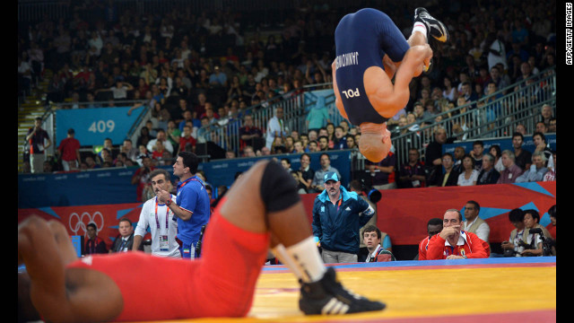 Damian Janikowski of Poland flips out as Pablo Enrique Shorey Hernandez of Cuba lies on the mat during the quarterfinal of the men's Greco-Roman 84-kilogram event.