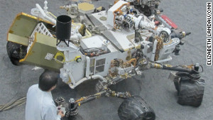 James Wang, test conductor for Curiosity, with the test model of the rover used for experiments on Earth.