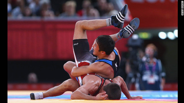 Ivo Serafimov Angelov of Bulgaria, bottom, competes against Almat Kebispayev of Kazakhstan, top, during the men's Greco-Roman 60-kilogram wrestling repechage.
