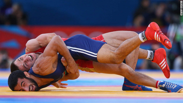 Zaur Kuramagomedov of Russia, in red, competes with Hasan Aliyev of Azerbaijan, in blue, during their men's Greco-Roman 60-kilogram wrestling bronze medal bout.