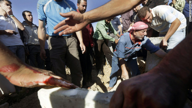 Syrian men bury their dead following heavy shelling by Syrian government forces in Qusayr, close to Homs, on July 3.<br />