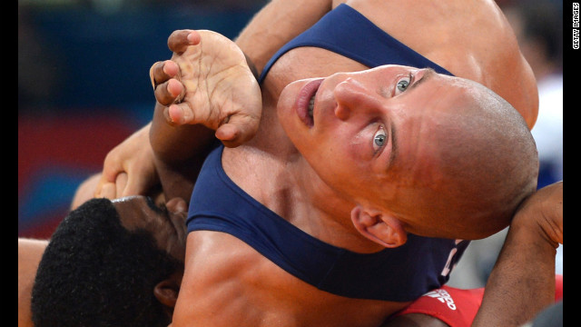 Damian Janikowski, in blue, of Poland can't believe that Cuban wrestler Pablo Enrique Shorey Hernandez is trying THAT.