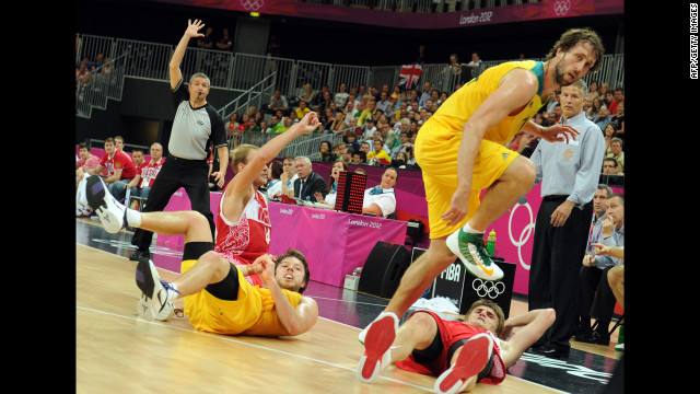 Australian, in yellow, and Russian players collide during the men's basketball preliminary round match.