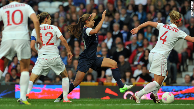 U.S. forward Alex Morgan, center in blue, runs with the ball past Canada's defender Lauren Sesselmann, number 10, forward Christine Sinclair, number 12, and defender Carmelina Moscato, number four, during the women's soccer semifinal match on Day 10 of the London Olympic Games on Saturday, August 4. Check out <a href='http://www.cnn.com/2012/08/05/worldsport/gallery/olympics-day-9/index.html' target='_blank'>Day 9 of competition</a> from Sunday, August 5.