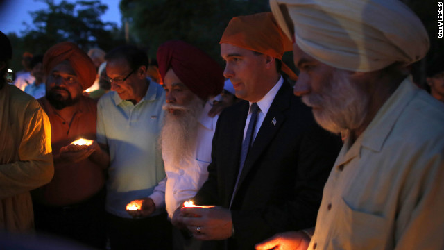 Wisconsin Gov. Scott Walker, along with members of the Sikh community, attend Monday's vigil at the Sikh Religious Society of Wisconsin for the victims of the shooting at the Sikh temple.