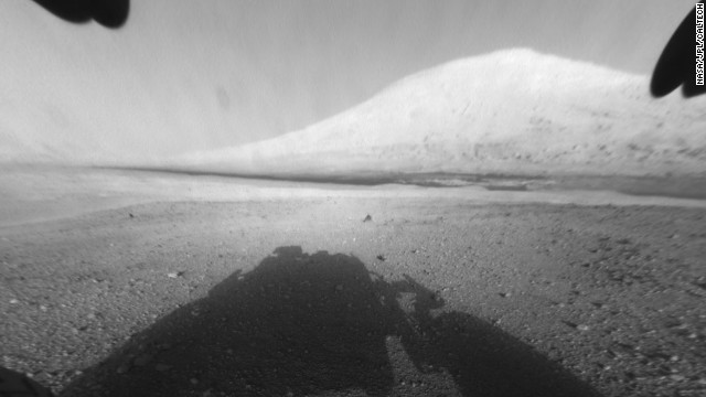 This image shows Curiosity's main science target, Mount Sharp. The rover's shadow can be seen in the foreground. The dark bands in the distances are dunes.