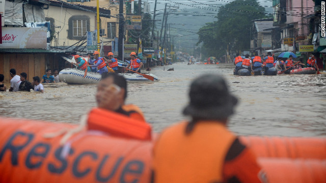 Rescuers maneuver down a flooded street as they evacuate residents in the village of Tumana in suburban Manila on Tuesday, August 7, after torrential rains inundated most of the capital.