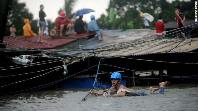 A man tries to cross floodwaters by following a rope as other residents wait on their roofs in Manila.
