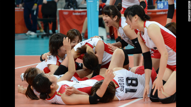 Japan's players celebrate their victory in the women's quarterfinal volleyball match against China.
